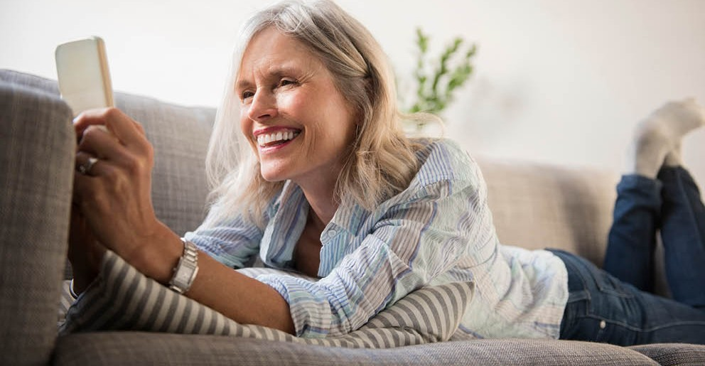 Old lady surfing on smartphone on couch